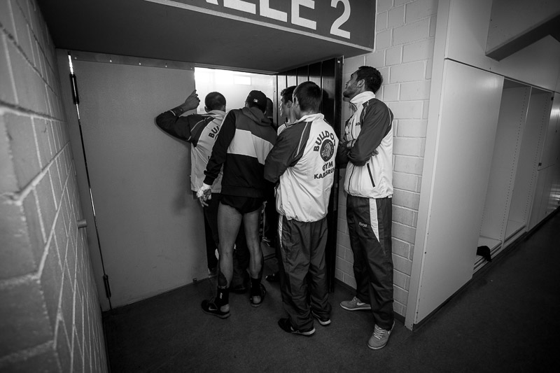 Fellow fighters and trainers watch an ongoing fight from the locker rooms.