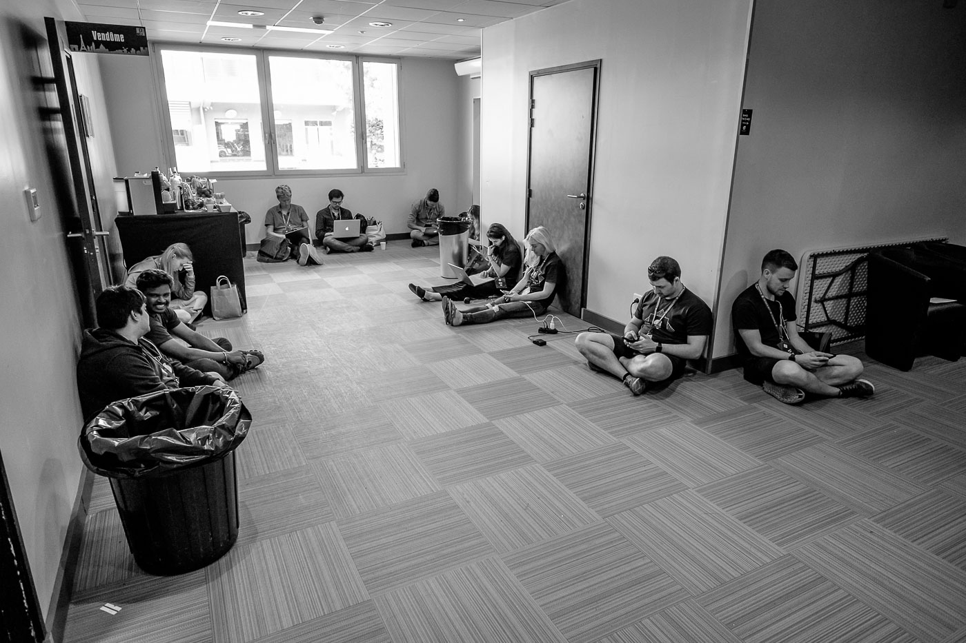 Volunteers sitting on the floor in the hallway backstage area