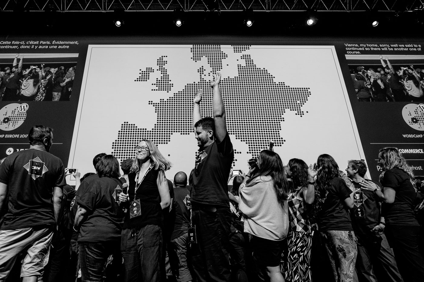 Emanuel raising his hands in the air, a crowd of volunteers and a huge map of Europe behind him
