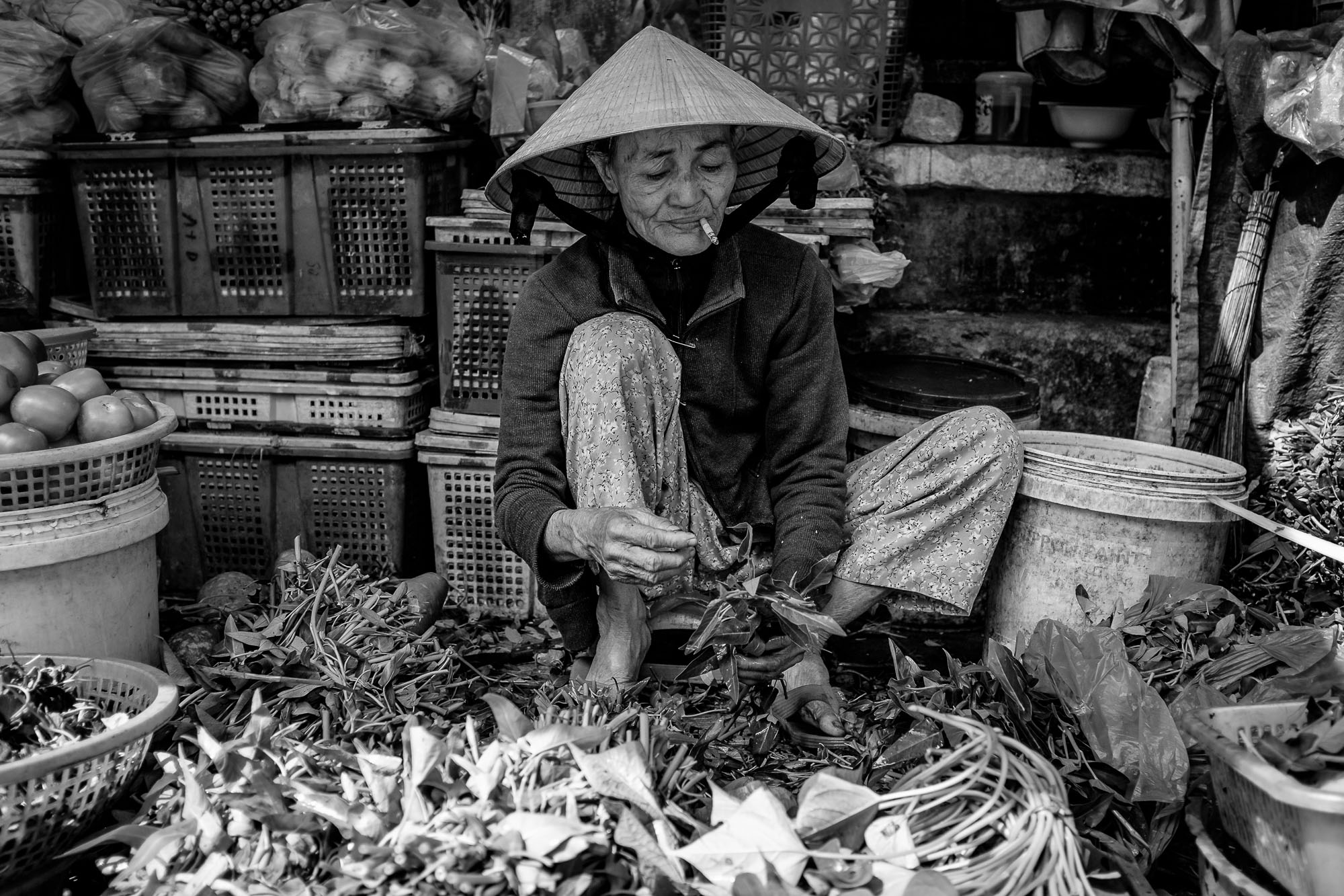 A Vendor is smoking and sorting through her goods