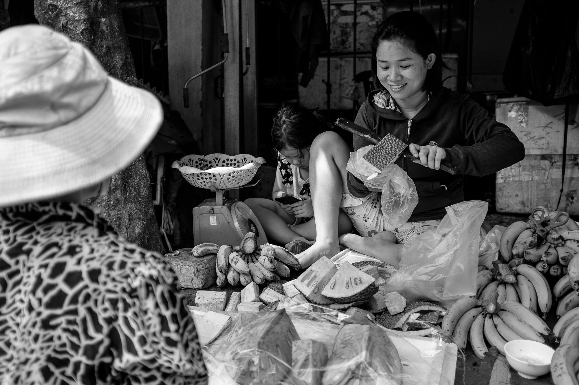 A vendor is cutting fruit, while her daughter is playing with her phone beside her