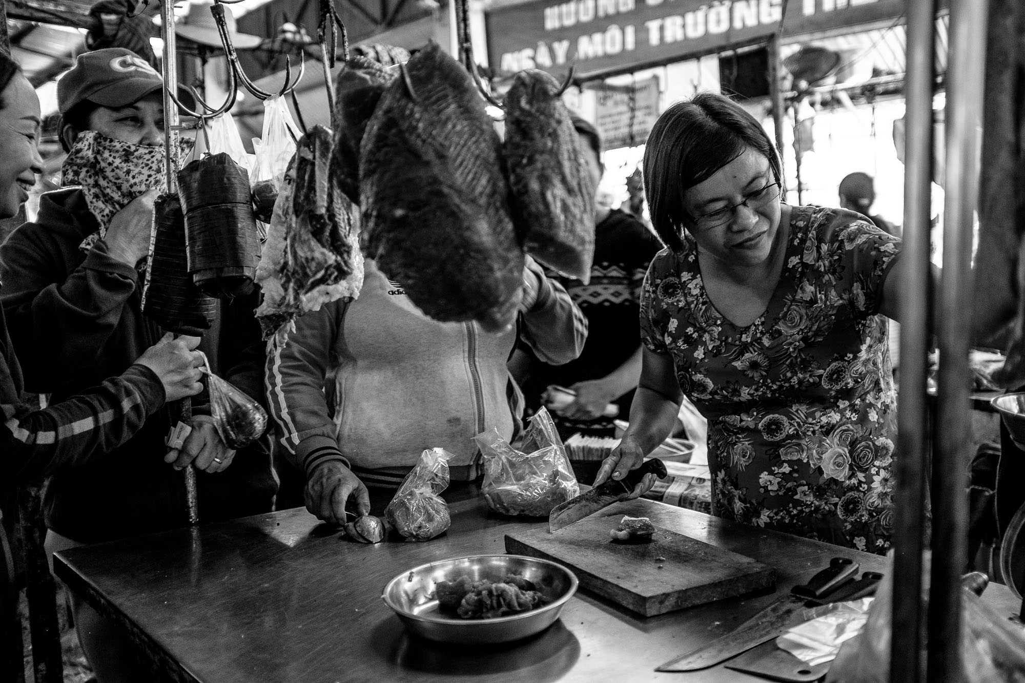 A vendor is cutting meat for wainting customers