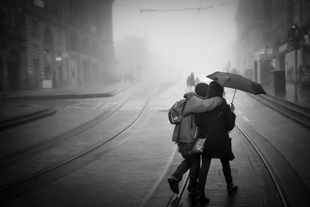 Couple under an umbrella walk the foggy streets of Edinburgh