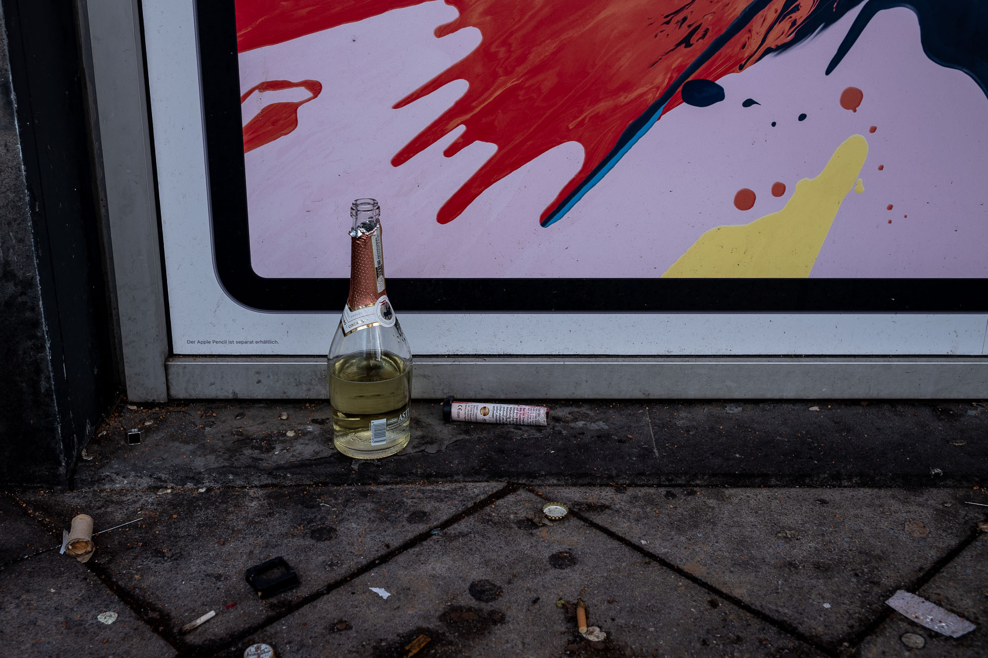 Half empty bottole of sparkling wine next to an colorful apple ad.
