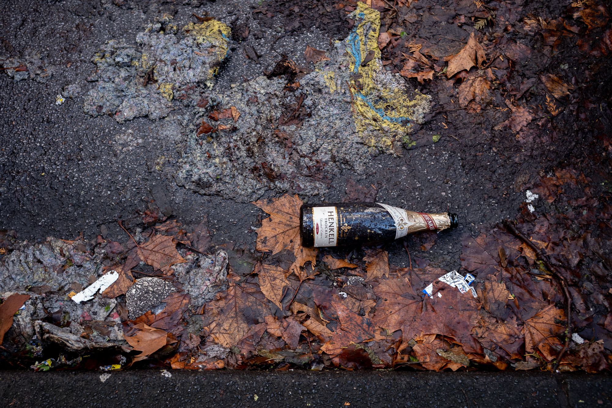 Empty bottle of sparkling wine and trash and wet, brown leafes on the street.